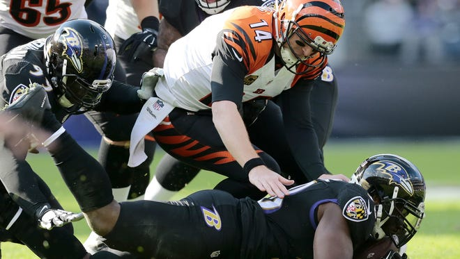 Cincinnati Bengals quarterback Andy Dalton (14) dives for a fumbled snap recovered by the Ravens in the second quarter of the NFL Week 12 game between the Baltimore Ravens and the Cincinnati Bengals at M&T Bank Stadium in Baltimore on Sunday, Nov. 27, 2016. After one half, the Ravens led the Bengals 16-3.