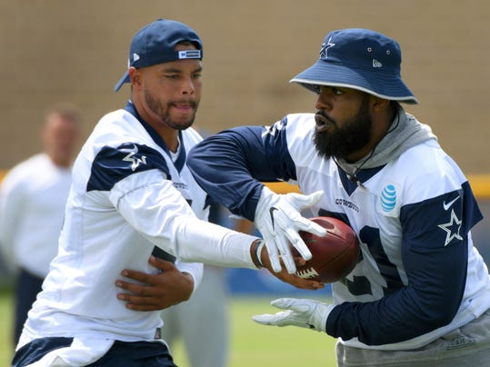 Dallas Cowboys quarterback Dak Prescott, left, hands off to running back Ezekiel Elliott during practice at the NFL football team's training camp in Oxnard, Calif., Monday, July 24, 2017. (AP Photo/Michael Owen Baker)