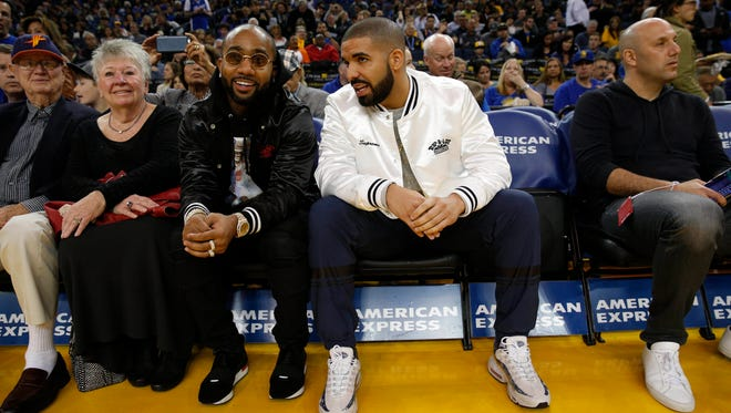 Music recording artist Drake (in white jacket) sits courtside before the start of a game between the Golden State Warriors and the New Orleans Pelicans at Oracle Arena.