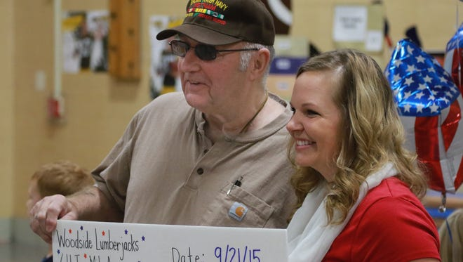 Bill Haack of Nekoosa stands with kidergarten teacher Brittney Lau at Woodside Elementary School in Wisconsin Rapids on Monday, Sept. 21, 2015, after Lau and students at Woodside donated $927.34 along with decorated plates and other items to Haack's American Heroes Cafe Central Wisconsin. The cafe will be hosted by the Lowell Senior Center in Wisconsin Rapids.