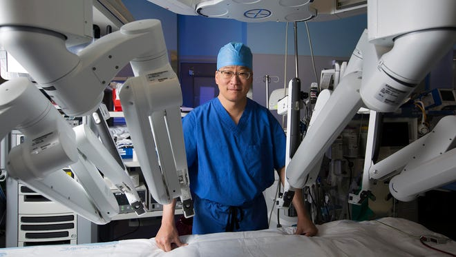 Leonard Y. Lee, M.D., Professor of Surgery at Rutgers Robert Wood Johnson Medical School and Chief, Division of Cardiothoracic Surgery at RWJUH, poses with the daVinci Xi robotic surgical system in an RWJUH operating room.