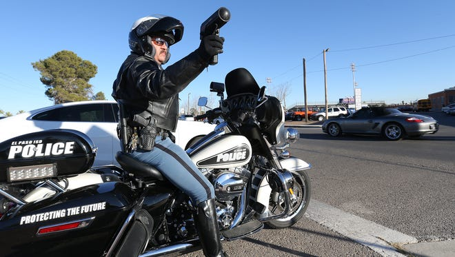 El Paso Independent School District police Lt. Zeke Garcia uses his radar device in the school zone outside Burges High School while looking for school zone violations Friday.