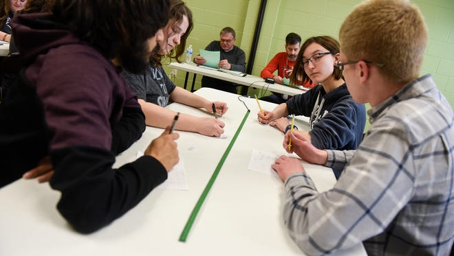 Members of the first-place Sauk Rapids team discuss an answer during the final round of Knowledge Bowl regional competition Monday, March 19, in Sartell.