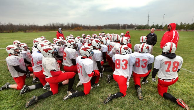 New Palestine High School head coach Kyle Ralph, right/red jacket, talks with his team before the start of practice on Wednesday, Nov. 12, 2014 in preparation for this weekend's Regional game against Roncalli.