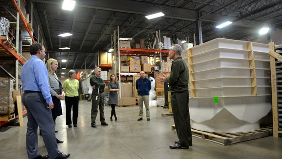 Neil Crocker, right, president of Schaefer Ventilation Equipment in Sauk Rapids, shows a stack of fan housings sourced from Litchfield during a visit Tuesday from DEED Commissioner Katie Clark-Sieben (second from left) and others on Tuesday. Times Business Reporter Kevin Allenspach is the one looking intent with arms folded.