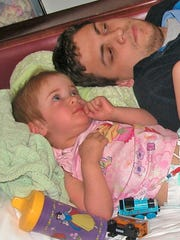 Dr. Adam Hill hangs out with a two-year old patient,