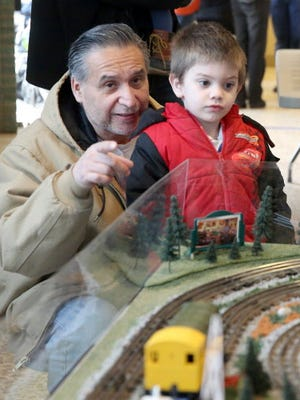 Robert Garcia points to parts of a layout as he watched with Ryder Garcia at the Mitchell Park Domes train show.