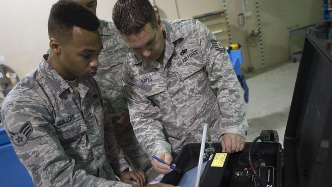 Senior Airman Devon Guillory and Tech. Sgt. Adam Hayes, 49th Maintenance Squadron aircraft structural maintenance technicians, analyze readings on a hot bonder, Dec. 14, 2016, at Holloman Air Force Base, N.M. The hot bonder adjusts the temperature for vacuum repairs on composite structures. Once the composite structure is repaired, it can be sanded, painted and returned to the aircraft.