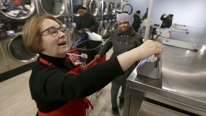 Volunteer Mary Jo Burgoyne (left) slides a pay card in a washing machine for Shawn Wells of Milwaukee, who was getting her laundry washed. The service, offered as part of Laundry Love, a national organization, gives people in financial need free laundry washing including detergent.