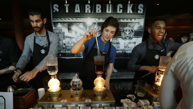 Starbucks workers prepare coffee using siphon vacuum coffee makers at a station in the lobby of the coffee company's annual shareholders meeting in Seattle. As Starbucks preps to overhaul its rewards program, some customers may be looking to take their money elsewhere.