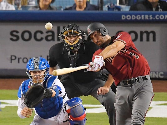 Arizona Diamondbacks' Adam Rosales hits an RBI double as Los Angeles Dodgers catcher Yasmani Grandal, left, watches along with home plate umpire Chad Fairchild during the seventh inning of a baseball game, Wednesday, Sept. 6, 2017, in Los Angeles. (AP Photo/Mark J. Terrill)