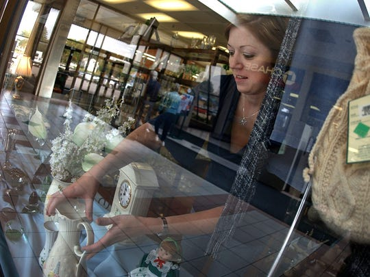 In this 2006 photo, Patricia Lloyd places a Belleek china vase in the showcase window as she restocks items at the Irish Import Shop when it operated in The Mall at Greece Ridge.