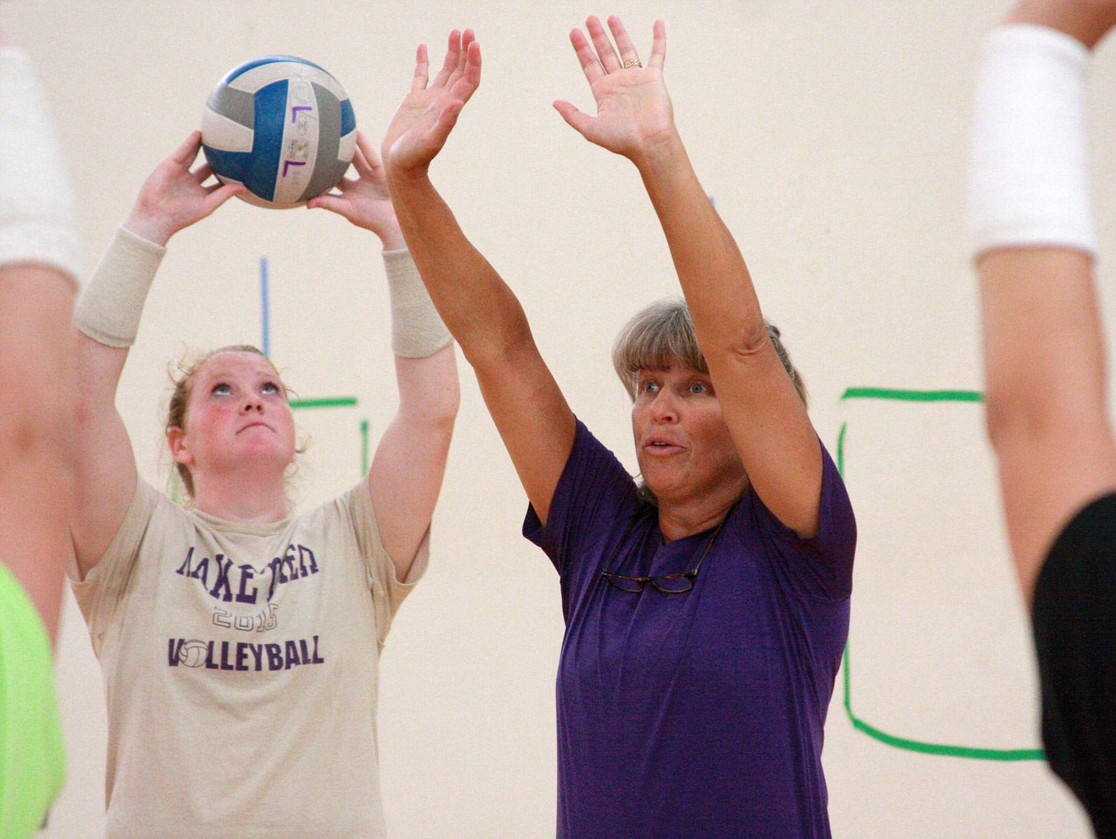 Lakeview varsity volleyball head coach Heather Sawyer shows the proper technique during a drill at team tryouts on Wednesday.