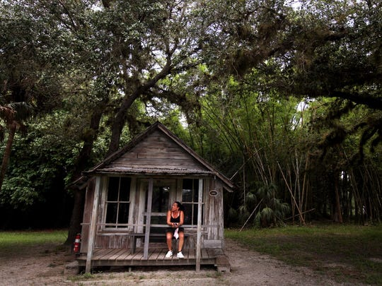 File: A visitor sits on the porch of one of the historic buildings at Koreshan State Park.