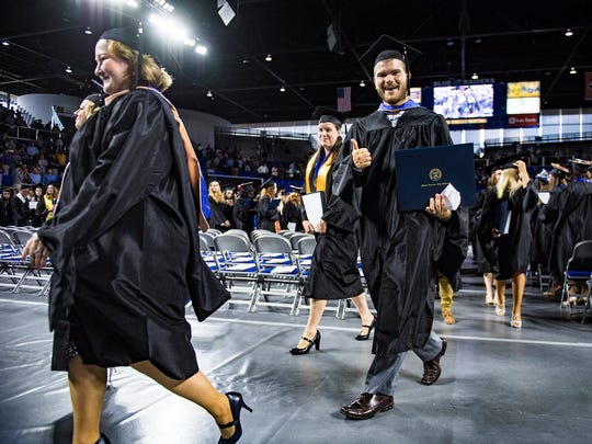An MTSU grad gives the thumbs up as the university's class of 2017 exits Hale Arena following Saturday's graduation ceremony.