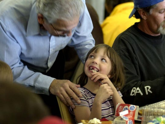 A child smiles after receiving a birthday cake on Christmas Day from Ray Trevino, director of St. Vincents Dinning Room. Barantley and her family were on hand Saturday at St. Vincents along with hundreds of others to eat a warm Christmas meal.