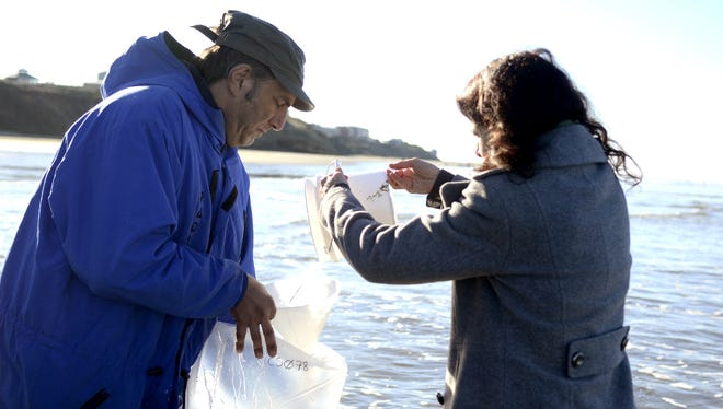 Terry Waldron and her husband, Andrew Rodman, collect seawater samples at Nye Beach in Newport in 2014. The samples were tested as part of a citizen-science Fukushima radiation monitoring project.