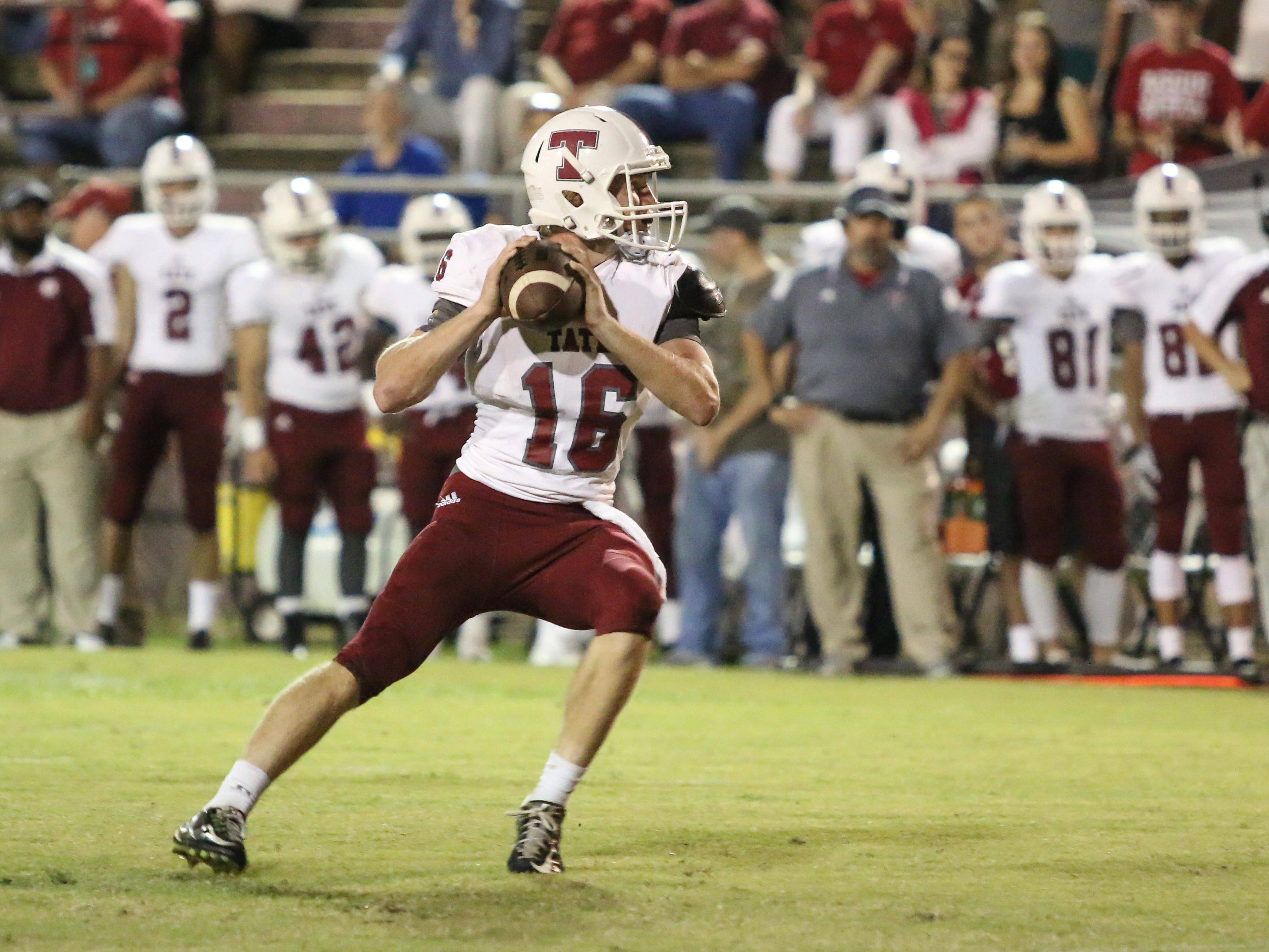 Tate quarterback Jake Henry (16) steps back and prepares to throw a touchdown pass to Rodriguez Smith during the opening drive of the game Friday night at Pensacola High School.