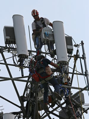 Technicians from Velex, a tower construction company contracted by Sprint, update antennas to create better coverage from a North Lynhurst Drive Sprint cell tower near Indianapolis Motor Speedway, Thursday, July 2, 2015, Indianapolis, Ind.