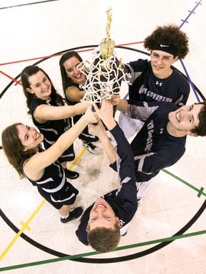 Clockwise from top right, New Covenant Christian School players Stuart Marshburn, Drew Milford, Reese Miller, Rebecca Lamb, Anna Milford, and Molly Landis, hold the boys SCISA state championship trophy. In two years, the school sent both boys and girls basketball teams to state championships.