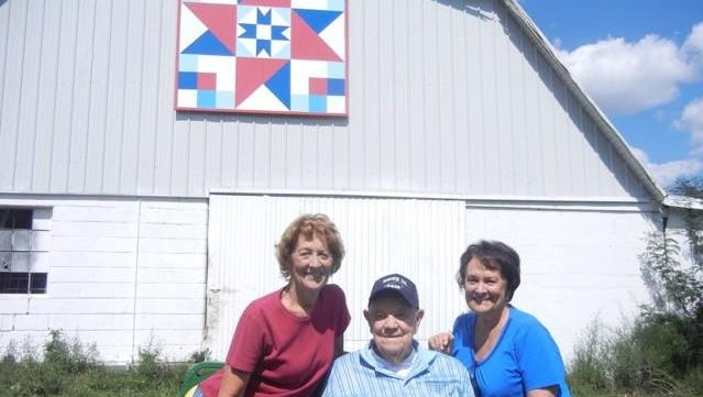 """From left, Sally Burcham, William (Bill) Graves, and Sue Spalding under their """"Twin Star"""" barn quilt, part of the Florence Woman's Club community service project called the Barn Quilt Trail."""