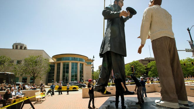 "A 31-foot-tall Abraham Lincoln, part of American realist Seward Johnson's ""Return Visit"" sculpture depicting Lincoln and a ""modern man"" holding a copy of the Gettysburg Address, is moved into position in front of the Abraham Lincoln Presidential Museum at the corner of Sixth and Jefferson streets in Springfield, Ill., Wednesday, May 22, 2019. The 31-foot-tall sculpture has been on view in Chicago, Troy, Ohio, and Peoria, Ill., and will stay in Springfield until September 2020."