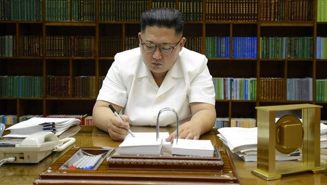 This July 27, 2017, photo released by North Korea's official Korean Central News Agency shows North Korean leader Kim Jong Un signing documents for the test launch of an intercontinental ballistic missile at an undisclosed place in his country.