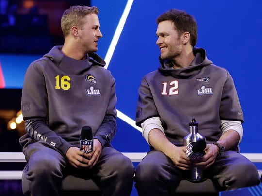 Rams' Jared Goff talks to Patriots' Tom Brady during Opening Night for Super Bowl 53 in Atlanta on Monday.