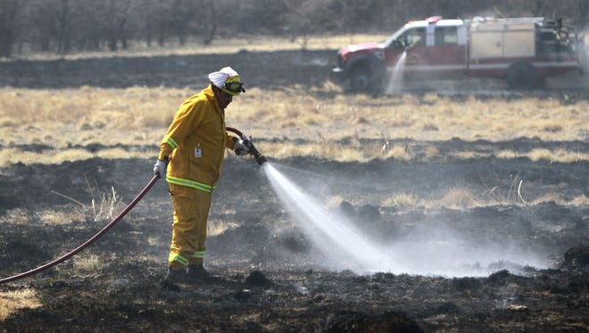 Chris Hare, a firefighter with San Juan County Fire Department District 2, works to extinguish a grass fire on March 29, 2014, at 720 County Road 3000 between Farmington and Flora Vista.