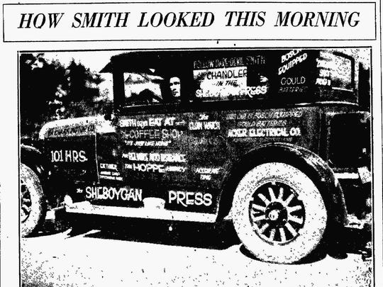 Smith in his Chandler car covered in advertising.