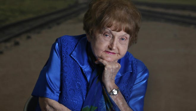"""Eva Kor sits before a photo of the arrival station at Birkenau, part of the Auschwitz death camp complex. Kor and her sister Miriam were """"Mengele twins,"""" singled out upon arrival at the camp for Dr. Joseph Mengele's medical experiments. Eva and her husband Mickey, who also survived a Nazi concentration camp, settled in Terre Haute, Ind., where she founded the C.A.N.D.L.E.S. Holocaust Museum."""