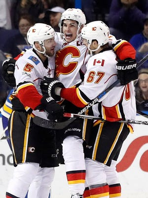 The Calgary Flames' Sean Monahan (center) is congratulated by teammates Mark Giordano  and Michael Frolik after scoring the game-winning goal in overtime.