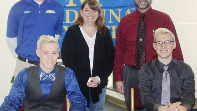 Wayne Memorial twin brothers Devin (seated left) and Michael Gibson signed letters of intent to run cross country for Madonna University. Also pictured are MU head coach Patrick Daugherty and the Gibsons' parents, Lisa and Tom.