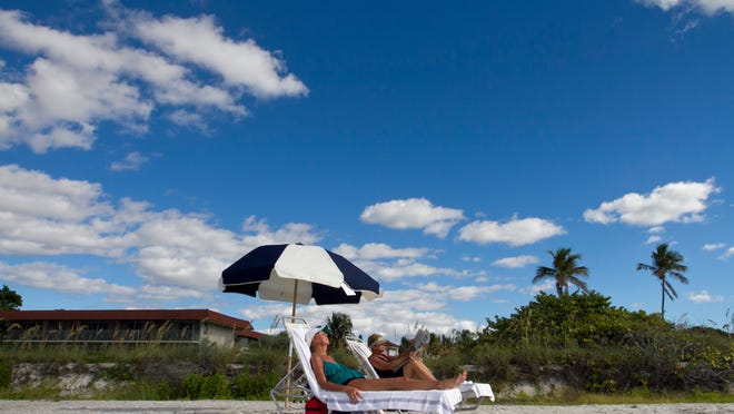 Brenda Harkleroad and Patty Cochran, of Knoxville, Tenn., relax on the beach Thursday at the West Wind Inn on Sanibel Islandursday. Many area hotels have special deals in the fall.
