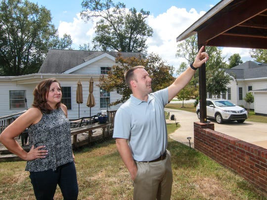 Heidi Landre watches her husband Eric point Friday to the carport that they want to convert into an enclosed garage. The couple are unhappy the cost of the garage may increase because of historic district rules prohibiting vinyl siding.