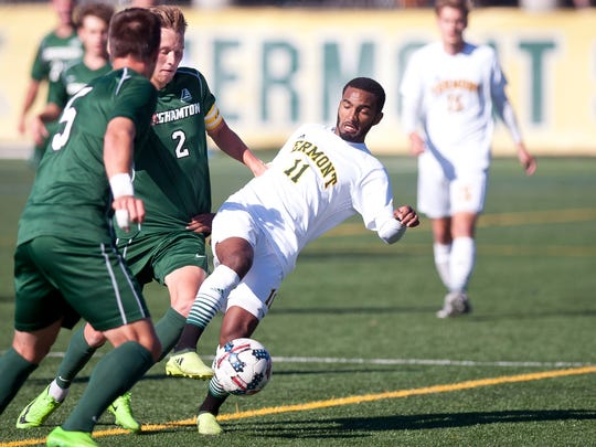 Vermont's Geo Alves, center, tries to control a ball under pressure from Binghamton defenders during Saturday's men's soccer game at Virtue Field.