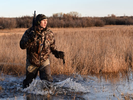 Karl Malcolm, a biologist with the U.S. Forest Service, retrieves a duck on Dec. 4.