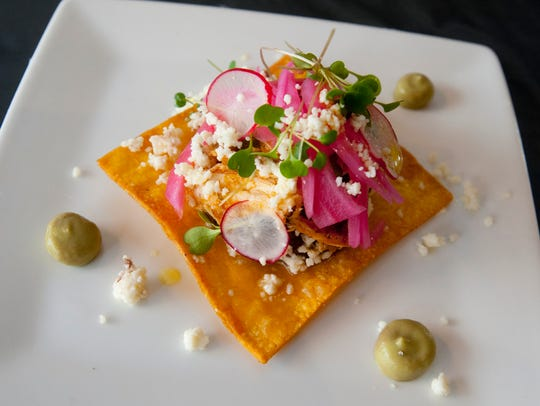 Chef Paco Garcia garnishes his chicken tinga with an
