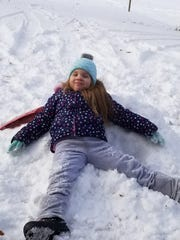 Emma Cheatham, seven, of Morganfield. sits in the snow