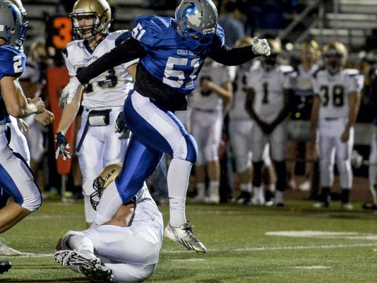 Cedar Crest's Garrett DeBien steps over Penn Manor's Grant Gale after recording a sack during the Falcons' 48-21 win over Penn Manor in their regular-season finale at Earl Boltz Stadium on Friday..