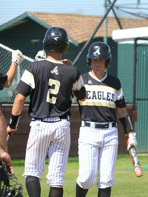 Abilene High's Andrew Ezzell, right, congratulates teammate Wes Berry after the latter scored a run during the Eagles' 15-0 win over Brownfield on Saturday at Blackburn Field.