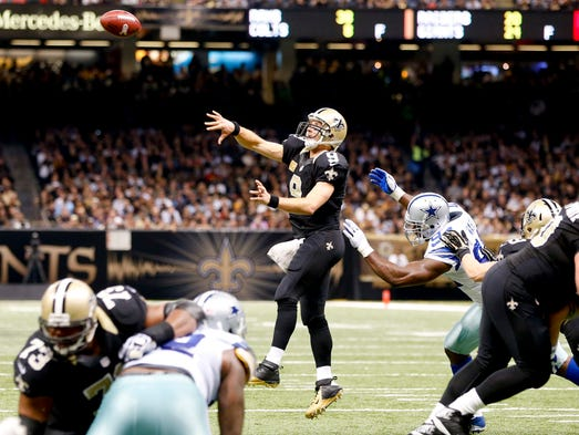 New Orleans Saints quarterback Drew Brees (9) throws a touchdown to running back Pierre Thomas (not pictured) as Dallas Cowboys defensive end DeMarcus Ware (94) pressures during the second quarter of a game at Mercedes-Benz Superdome.