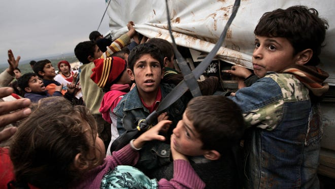 In this 2012 photo, Syrian children who fled their homes gather around a vehicle to get pillows and blankets distributed at a camp for displaced Syrians.