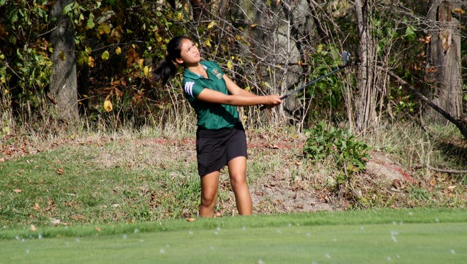 Anci Dy, of Traverse City West, chips at the 9th green at The Meadows at Grand Valley State University on Friday, Oct. 20, 2017.