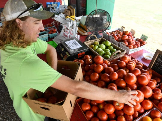 Jackson Campbell stocks ripe tomatoes at the Reinmann Farm vegetable stand along Darmstadt Road Wednesday, July 26, 2017.