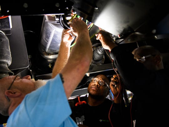 From left, Dennis Davis, Terry Collins and Keith Drummond actuate exhaust valves on an electric bus at the Proterra plant in Greenville.