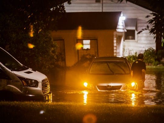 A man wades through flood water to check on a car stalled in the intersection of 56th Street and New York Avenue after a flash flooding on June 30 in Des Moines.