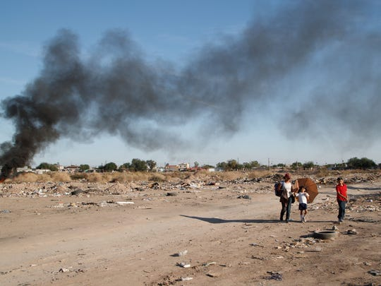 A woman walks two children home from school through a lot where trash is burning in Mexicali, Baja California, Nov. 16, 2017.