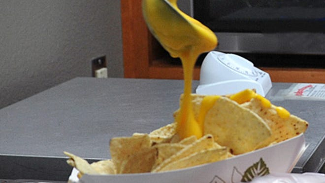 Nacho cheese is poured on tortilla chips.