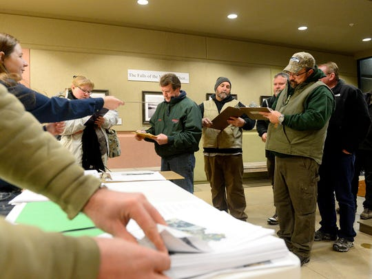 People sign in before the Fish, Wildlife and Parks